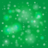 Snowflakes and blurry lights on green background Royalty Free Stock Photo
