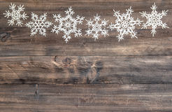 Snowflakes border over wooden background. christmas decoration. Snowflakes border over rustic wooden background. christmas decoration Royalty Free Stock Photos