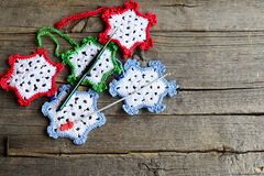 Snowflakes crocheted from cotton yarn, two hooks on an old wooden background with copy space for text. Easy winter crafts. Easy winter crafts for children and royalty free stock image