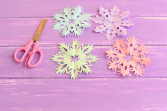 Snowflakes cut from colored paper. Pink, green, blue and purple paper snowflakes, scissors on wooden table. Children winter crafts Stock Photos