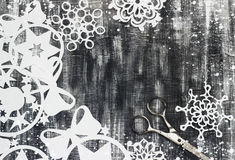Snowflakes cut out of paper on dark background with space for text Christmas theme Stock Image