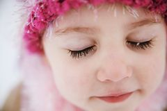 Snowflakes on eyelashes. Young girl with snowflakes on long dark eyelashes wearing a hat outdoors in winter Royalty Free Stock Image