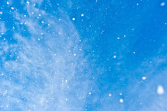 Snowflakes falling from blue sky Stock Image