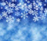 Snowflakes falling, light blue background stock photos