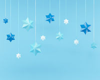 Snowflakes and a garland of 3d stars on blue background with clipping path Royalty Free Stock Image