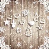 Snowflakes and hanging toys on the wooden board background. Royalty Free Stock Photos