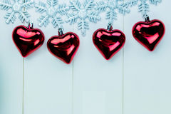 Snowflakes and heart ornaments hanging on white wood background Stock Images