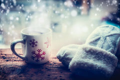 Snowflakes Mug with hot beverage and knitting mittens on frost window sill at winter snow nature Stock Images