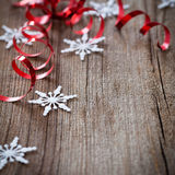 Snowflakes and red ribbons on wood Stock Image