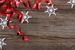 Snowflakes and red ribbons on wood Royalty Free Stock Image