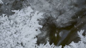 Snowflakes on the rocks in the river stock footage