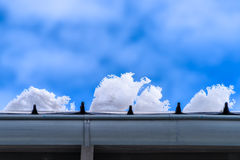Snowflakes on rooftop against blue winter sky Stock Image