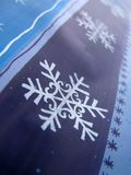 Snowflakes and stars. Big snowflake and lot a small stars on blue paper (wrapping Royalty Free Stock Images