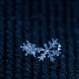 Snowflakes on textured fabric. Two beautiful snowflakes are nestled together on blue textured fabric Royalty Free Stock Photos