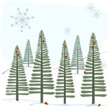 Snowflakes and trees. A winter scene with pine trees in the snow with snowflakes starting to fall Royalty Free Stock Image