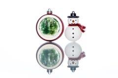 Snowglobe con el árbol de navidad dentro con el muñeco de nieve en Backg blanco Imagen de archivo