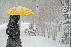 Snowing. Woman sheltering from heavy snow under a yellow umbrella Royalty Free Stock Image