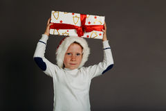 Snowing Christmas photo of funny little boy with the gift-box Stock Photos