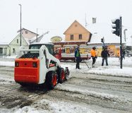 Snowing in city. Clear up street to reduce traffic jam, wintertime, Europe Stock Image