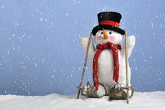 Snowing on cute snowman on skis Royalty Free Stock Photography