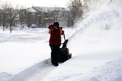 Snowing day young boy blowing snow Royalty Free Stock Images