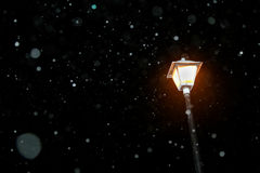Snowing Falling by Lamp Light Stock Photo