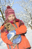 Snowing with flakes on girl and dog. White child having fun with baby animal in winter season Stock Image