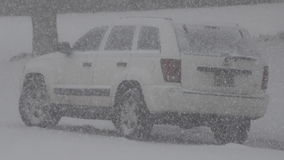 Snowing a White Jeep Car. Closeup of a jeep truck taking a lot of heavy snow stock footage