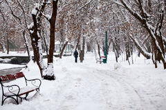 Snowing landscape in the park with people passing by Royalty Free Stock Images
