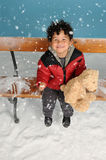 Snowing on a little boy. Seated on a bench stock images