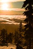 Snowing through magical sunrise. Snow falling through a magical sunset on top of the clouds and mountains Royalty Free Stock Photo