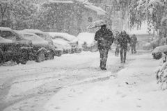 Snowing miastowy krajobraz z ludźmi przechodzi obok Fotografia Royalty Free