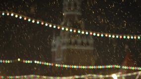 Snowing. multi-colored Christmas garlands on the background of the Kremlin s Spassky tower. stock footage