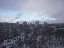 It is snowing over the city. In the early winter cloudy afternoon Royalty Free Stock Image