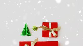 Snowing over gift boxes and christmas tree origami stock footage