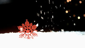 Snowing on a red snowflake. Against a black background stock footage