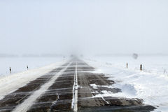 Snowing Road. In the middle of snow fields royalty free stock photo