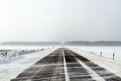 Snowing Road. In the middle of snow fields Royalty Free Stock Photography