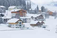 Snowing in snow covered winter village. In austria Royalty Free Stock Image