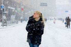 Blonde woman in fur coat walking. Snowfall. Snowfall in Kiev - Blonde girl walking at Khreschatick royalty free stock photography
