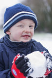 Snowing today. Boy holding a snow ball and it is snowing Royalty Free Stock Images