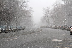 Snowing urban landscape with cars. On a parking lot Royalty Free Stock Photography