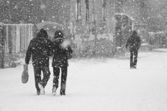 Snowing urban landscape with people passing by Stock Photo