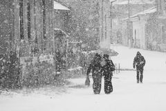 Snowing urban landscape with people passing by Royalty Free Stock Photos