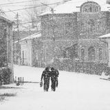 Snowing urban landscape with people passing by Royalty Free Stock Photography
