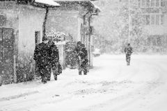 Snowing urban landscape with people Royalty Free Stock Photo