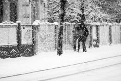 Snowing urban landscape with people Royalty Free Stock Image