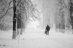 Snowing urban landscape with people Stock Photos