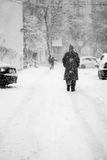 Snowing urban landscape with people Stock Images