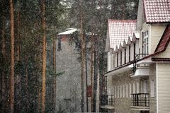 Snowing with view on forest house and tower Stock Photo